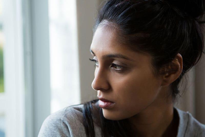 jeune femme triste par la fenêtre