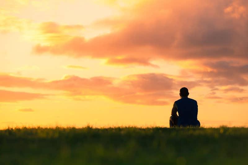 jeune homme solitaire au coucher du soleil