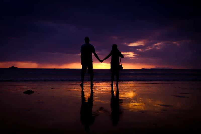 silhouette d'un couple marchant sur la plage