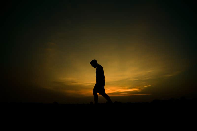 silhouette d'un homme triste au coucher du soleil