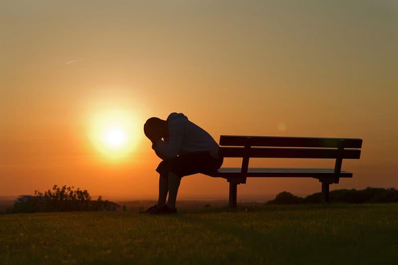 silhouette d'un jeune homme triste sur banc