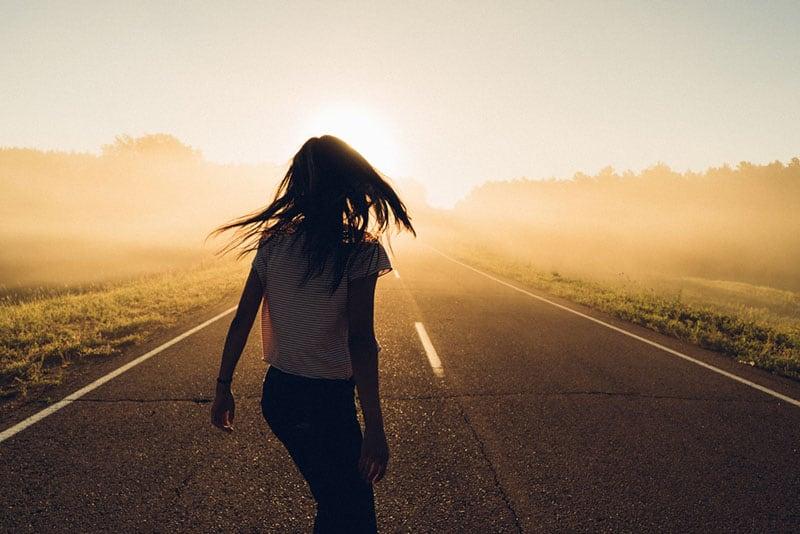 silhouette d'une jeune femme sur route