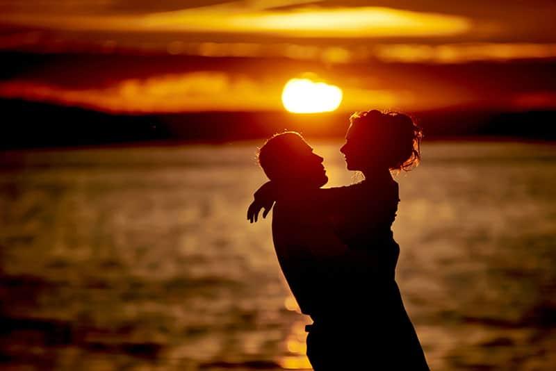 silhouette, jeune, couple, étreindre, Coucher soleil