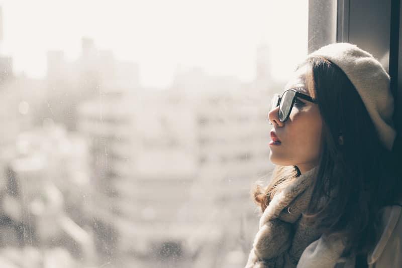triste jeune femme asiatique par la fenêtre