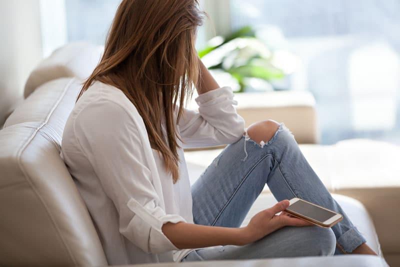 triste jeune femme avec un téléphone sur le canapé