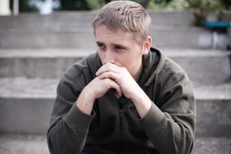 triste jeune homme assis dans les escaliers