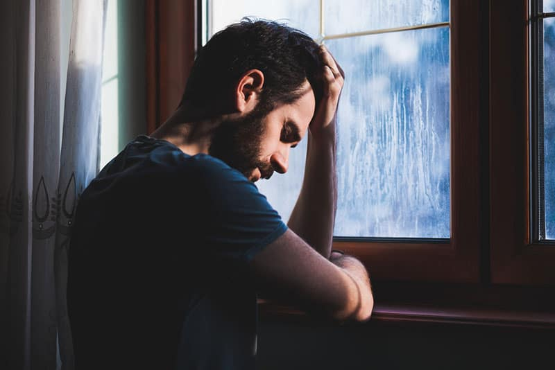 triste jeune homme près de la fenêtre