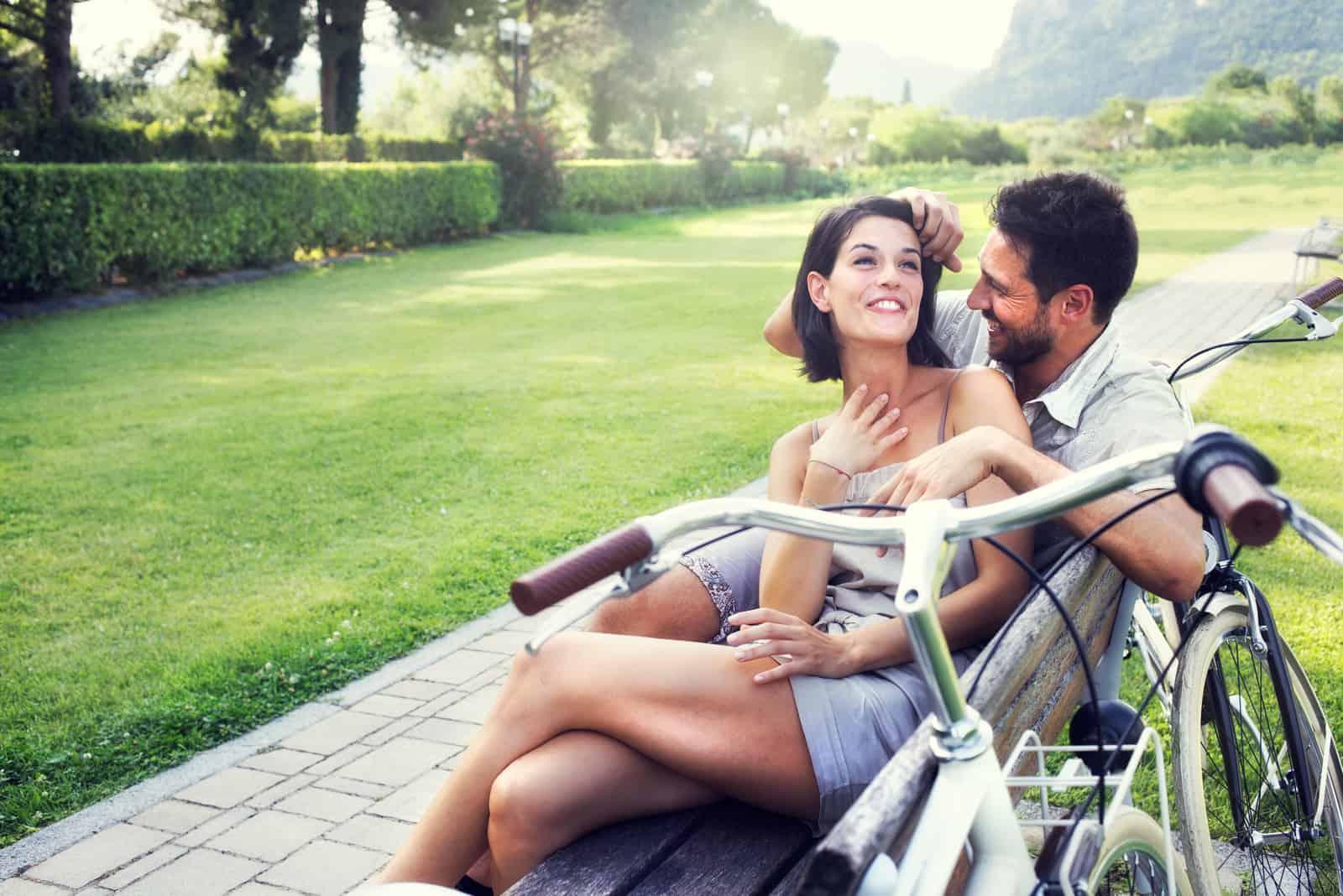 un homme et une femme s'embrassant en train de parler sur un banc de parc