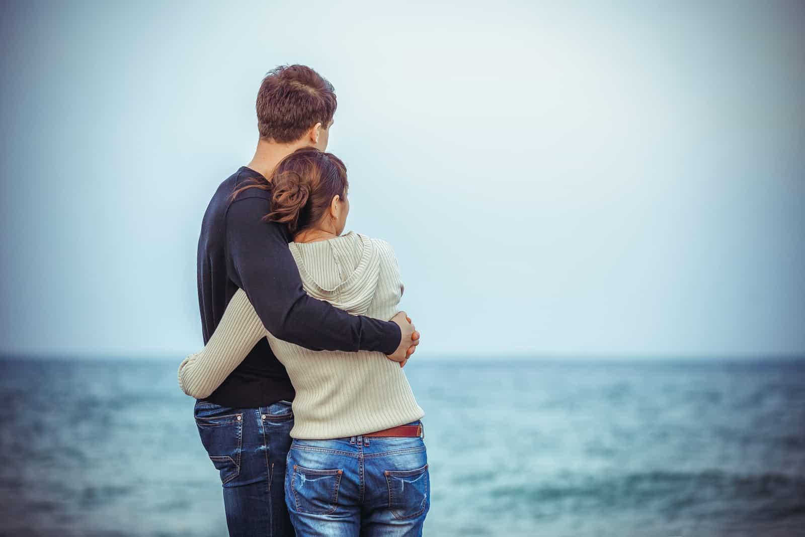 un homme et une femme s'embrassent en regardant la mer