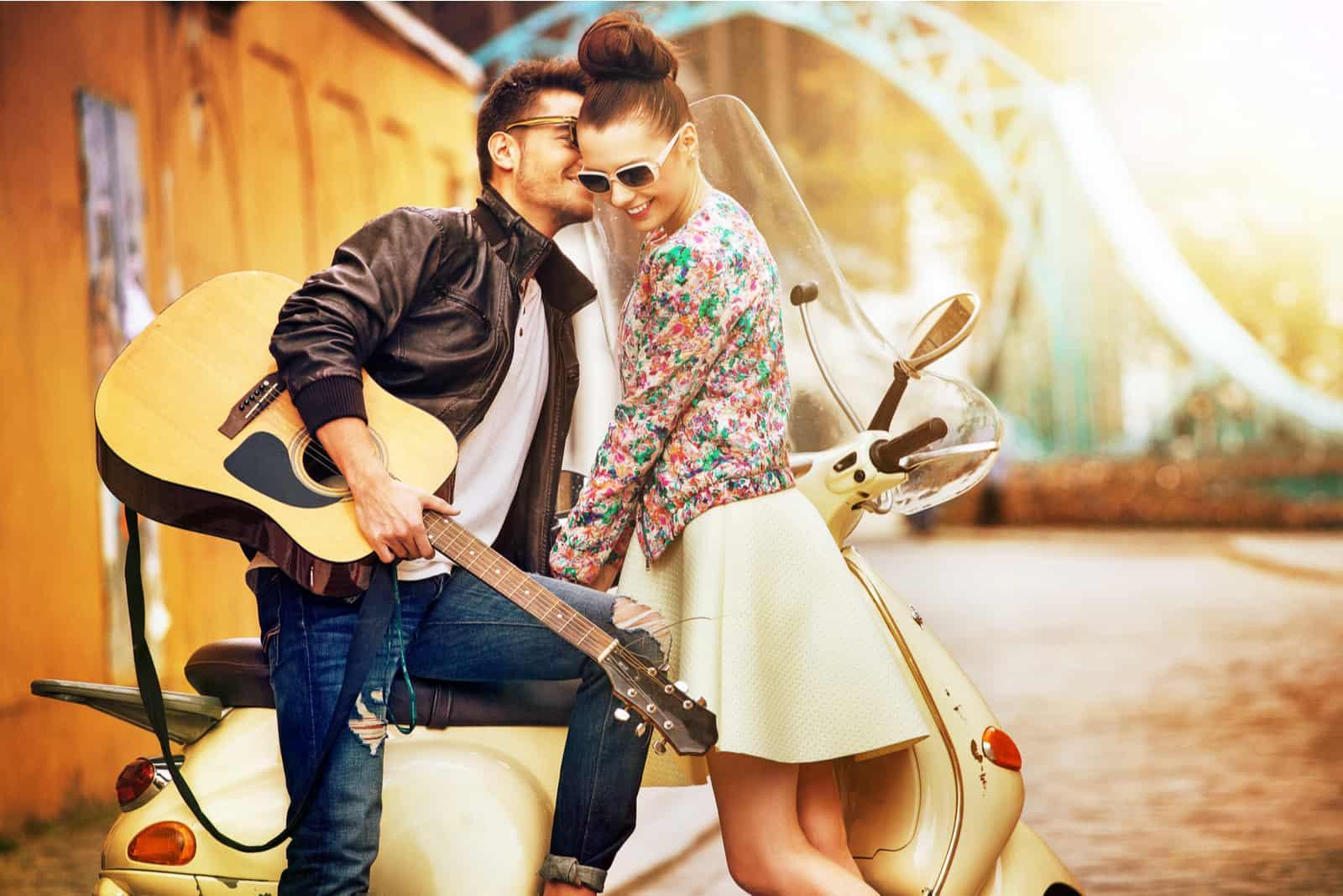 un homme s'appuyant sur un vélo embrasse une femme sur la joue