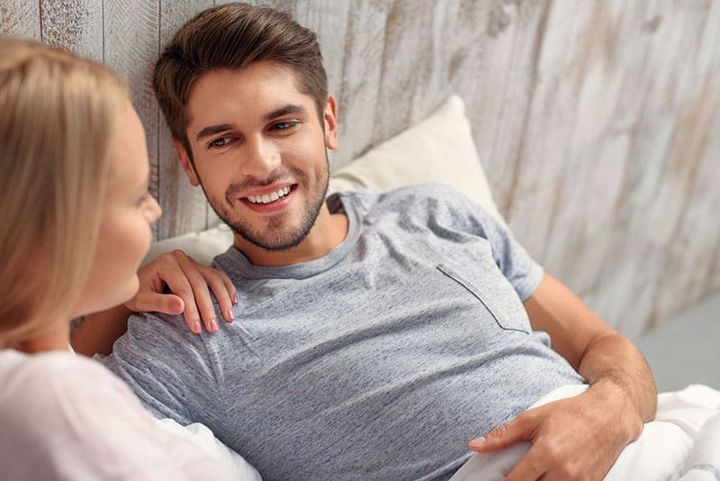 jeune couple, dans lit, sourire