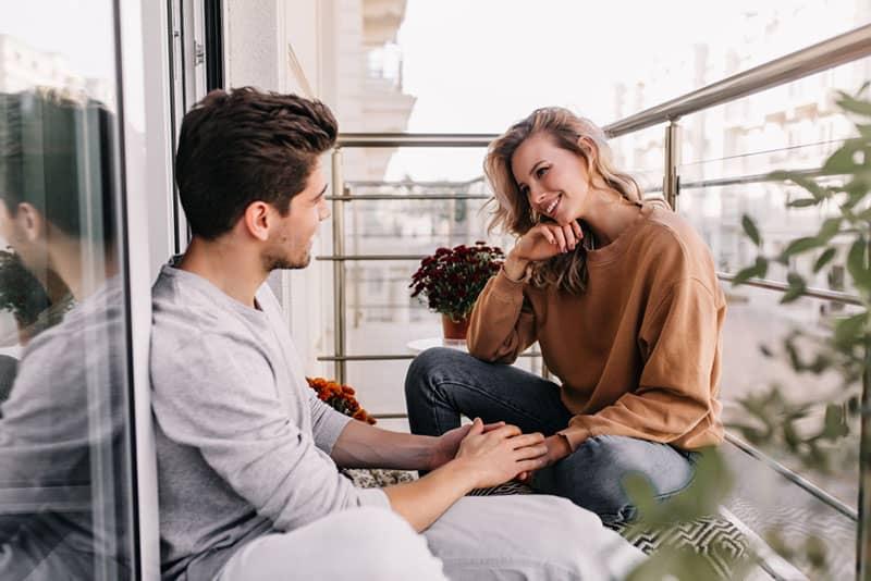 couple heureux parler sur balcon