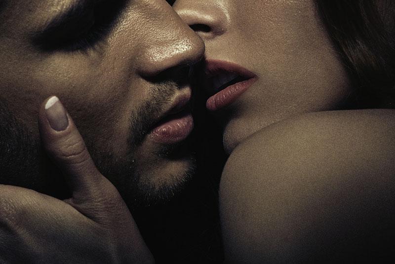 couple sensuel s'embrassant dans l'obscurité