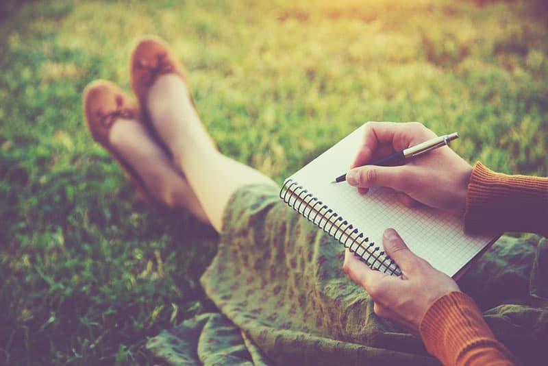 femme écrivant sur son petit cahier