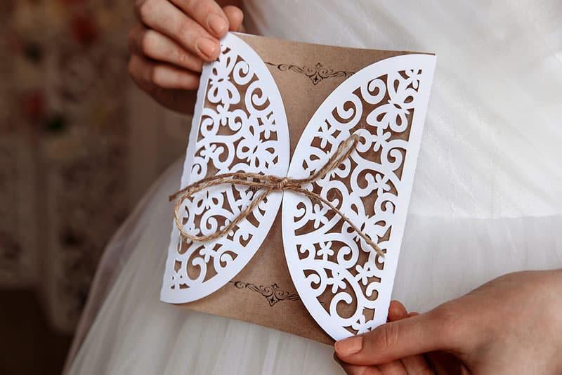 femme en blanc tenant invitation
