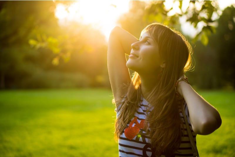 femme heureuse, debout, dans, lumière soleil