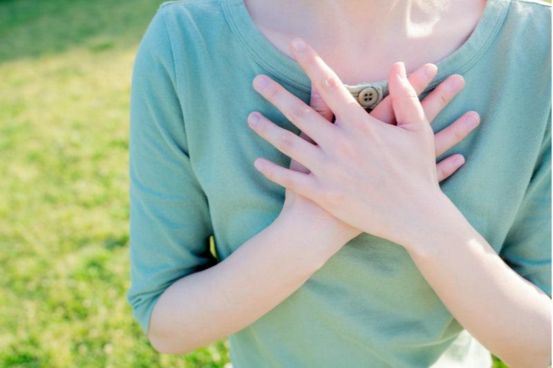 femme tenant les mains sur la poitrine