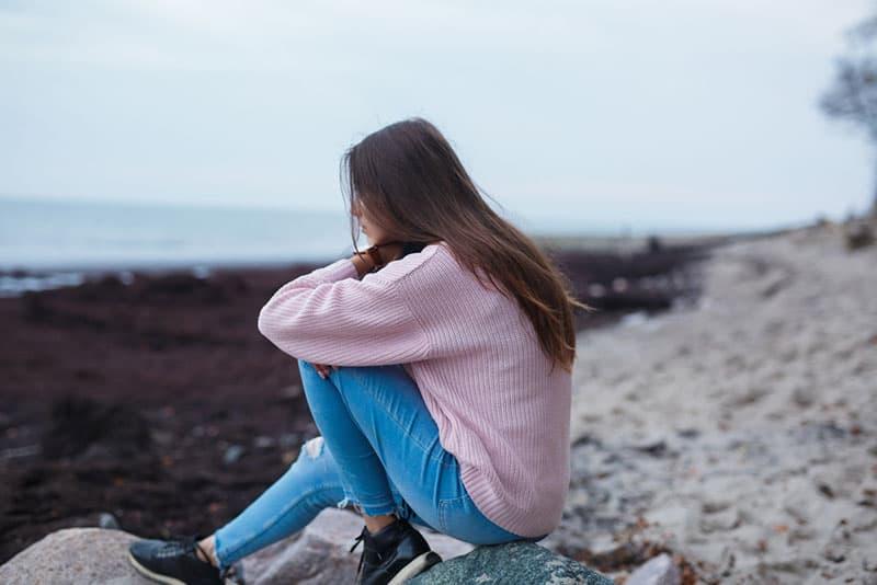 femme triste assise sur la plage