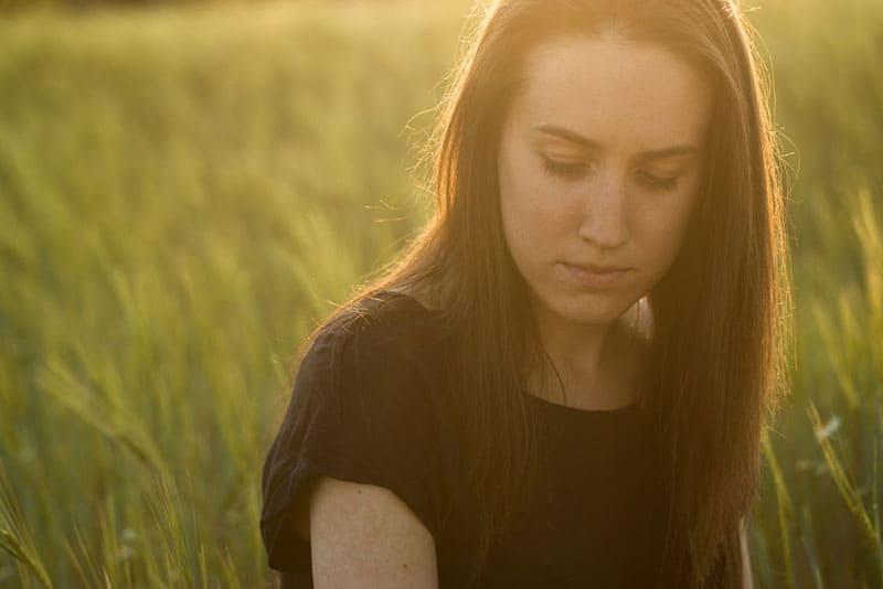 femme triste au coucher du soleil dans le champ
