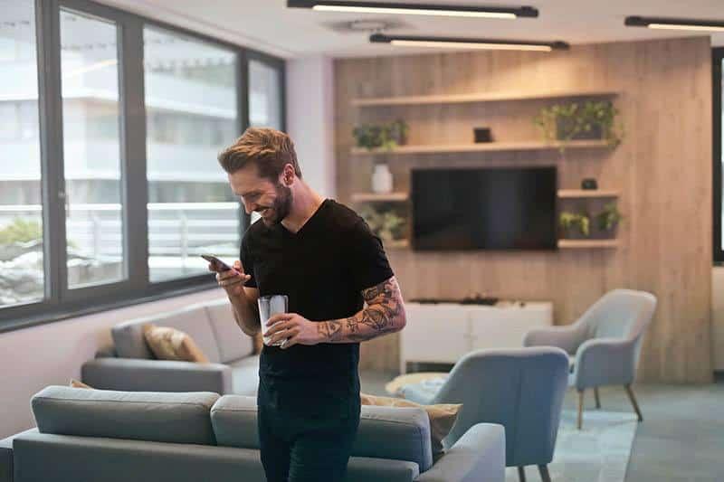 homme joyeux tient verre et regarde son téléphone