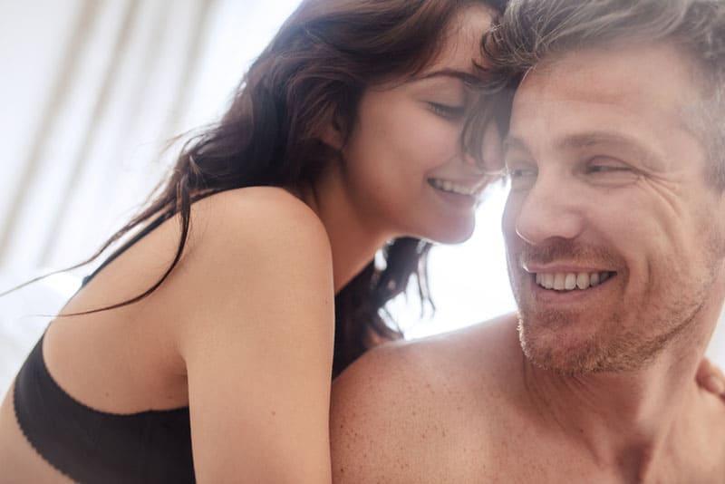 jeune couple, étreindre, dans lit