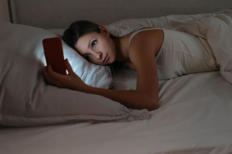 jeune femme, téléphone, dans lit