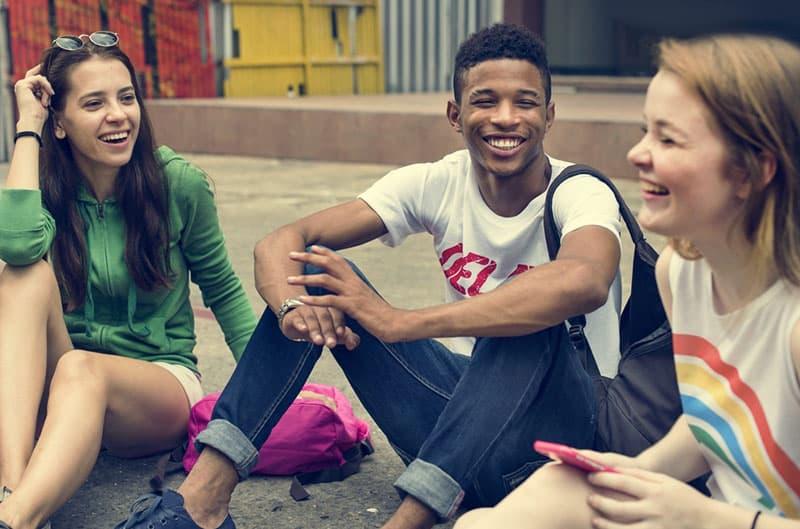 jeunes amis rire et assis sur le sol