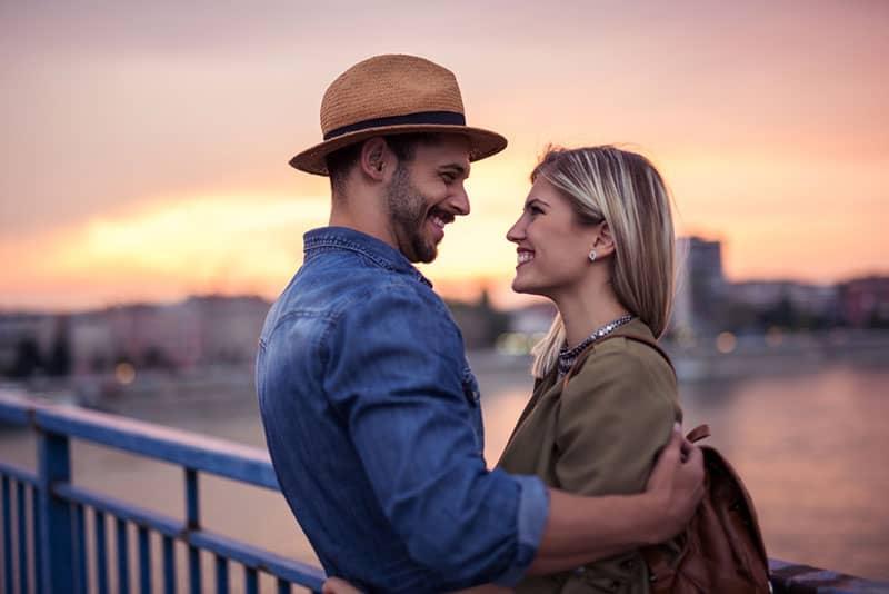 joli couple au coucher du soleil sur le pont