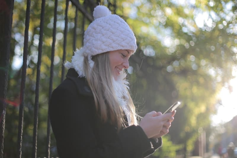 la femme tient le téléphone et écrit