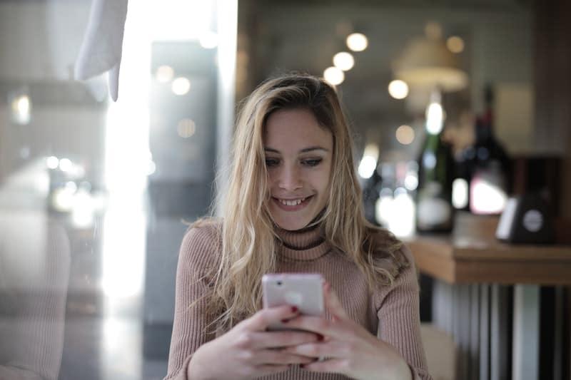 une femme joyeuse regarde le téléphone