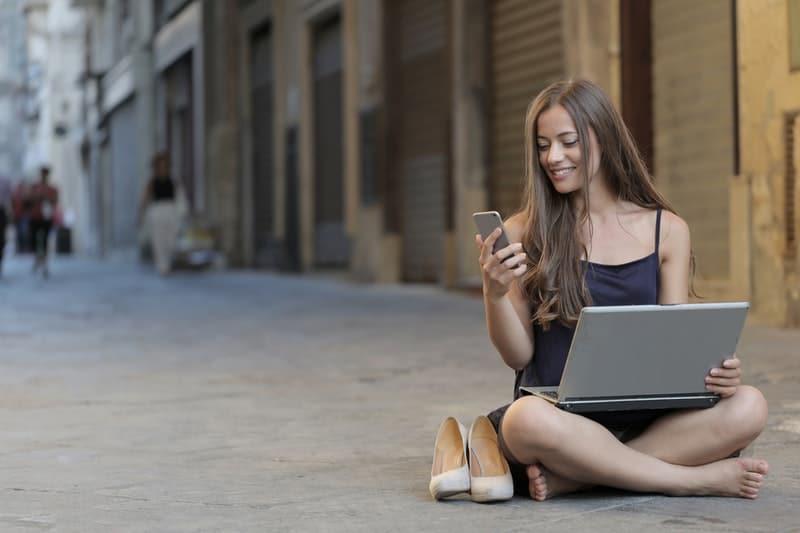 une femme souriante assise sur le béton