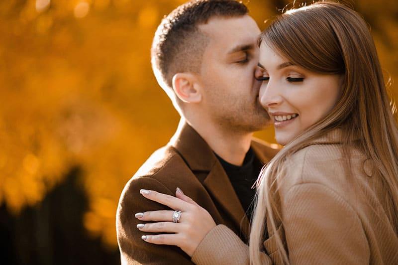 couple heureux s'embrasser en automne