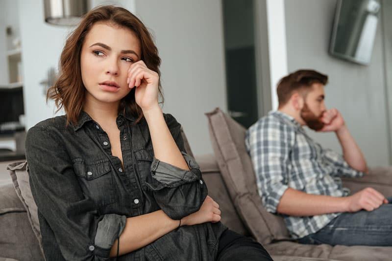 femme triste avec son petit ami sur le canapé