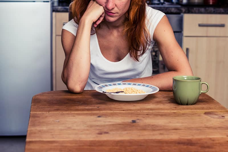 femme triste, manger dans la cuisine