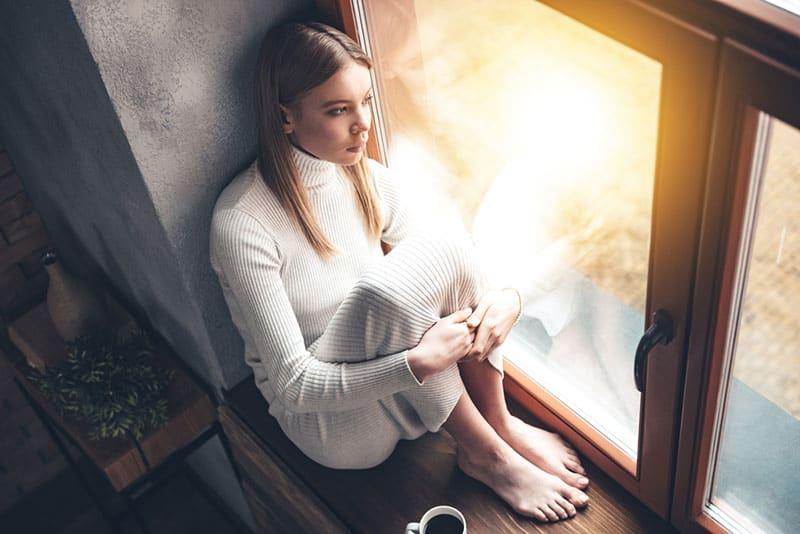 triste jeune femme blonde par la fenêtre