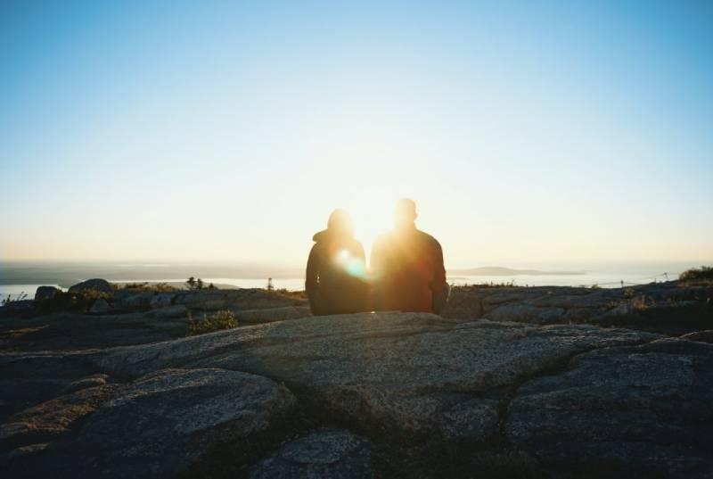 un homme et une femme sont assis sur une pierre