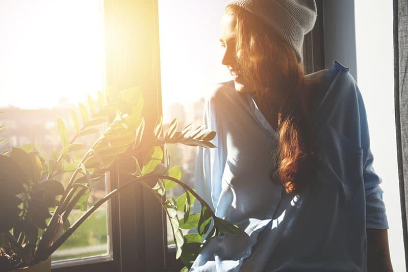 heureuse jeune femme souriante par la fenêtre