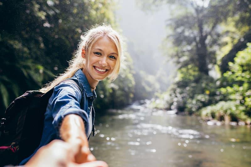 heureuse jeune femme blonde tenant la main dans la nature