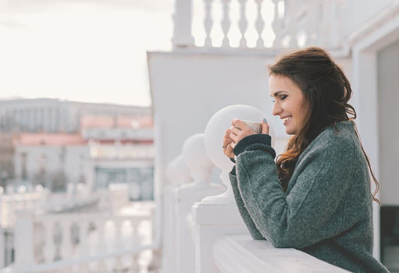 joyeuse jeune femme buvant du café sur le balcon