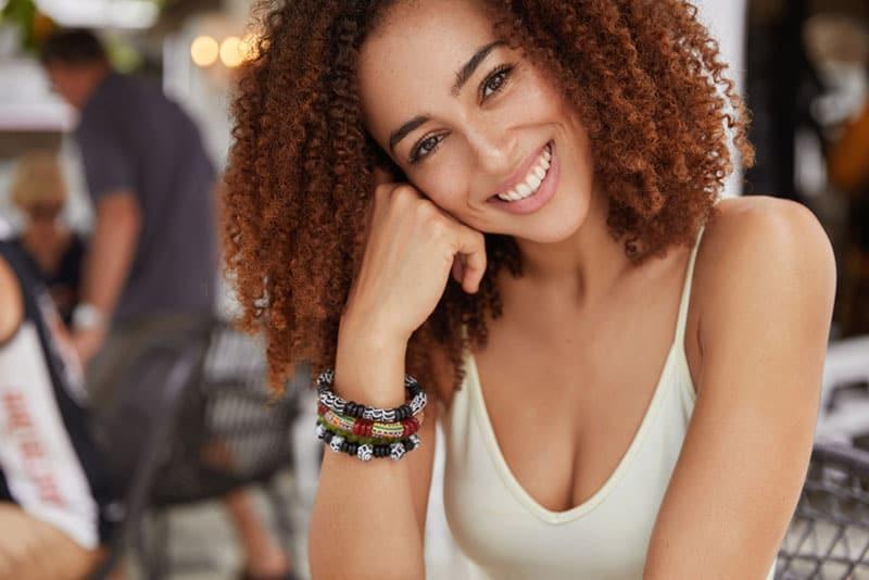 heureuse jeune femme noire avec des boucles