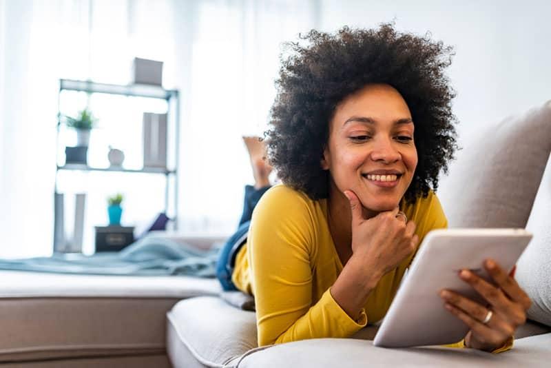 heureuse femme noire avec téléphone sur le canapé