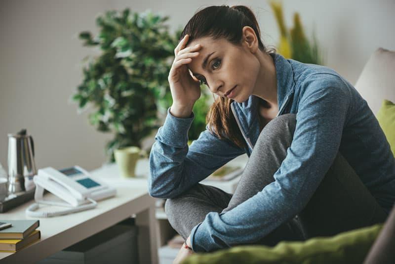 femme triste avec sa main sur sa tête assise sur le canapé