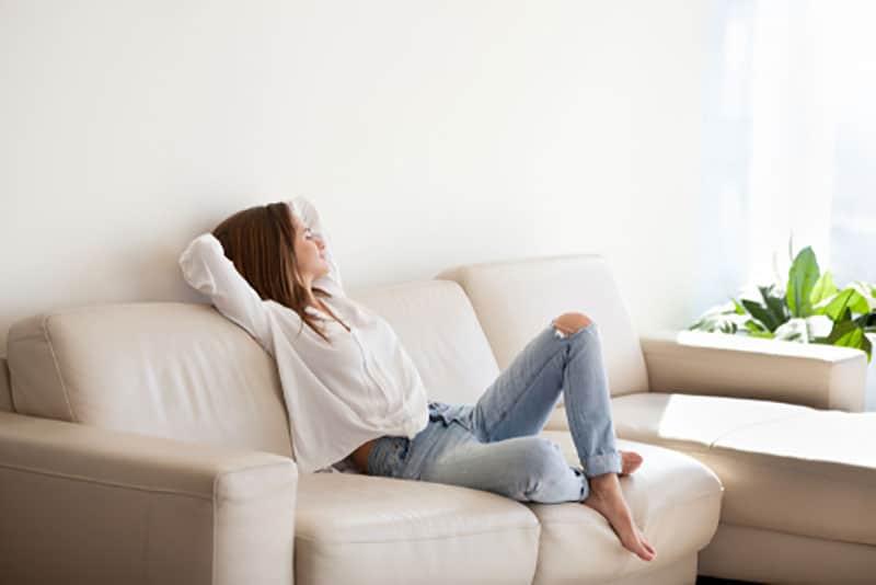 femme heureuse se détendre sur le canapé