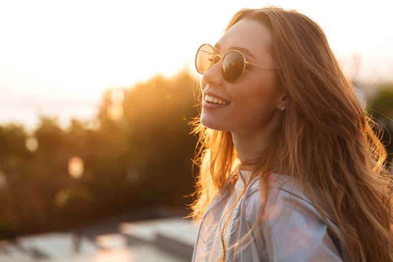 jeune femme souriante au coucher du soleil