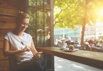 femme heureuse au bar à café en regardant son téléphone