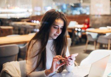 SMS fille sur téléphone en bar