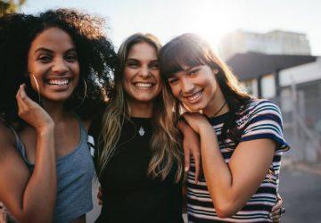 Trois jeunes filles souriantes posent à l'extérieur