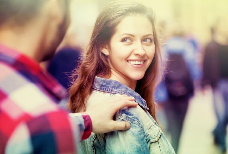 Un jeune homme arrête une belle femme heureuse dans une rue