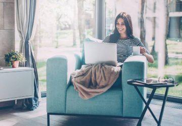 Femme s'asseyant sur l'ordinateur portatif de saisie de sofa et souriant