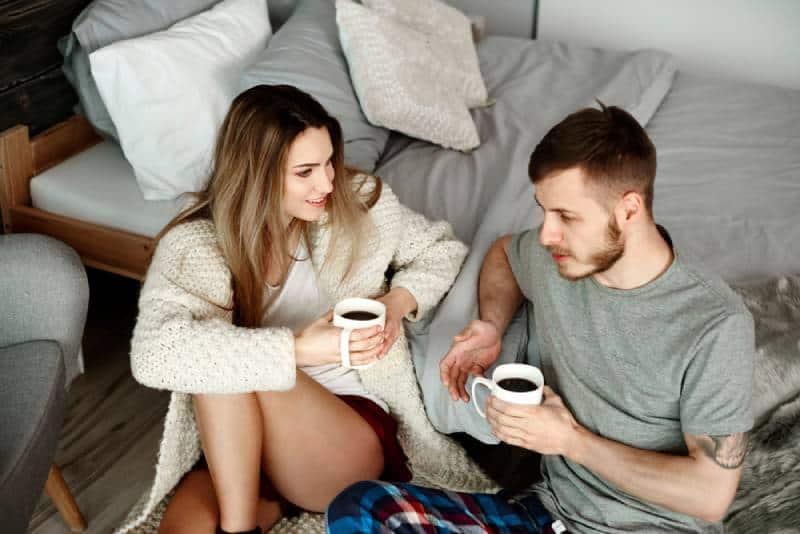 Couple avec café assis par terre et discutant
